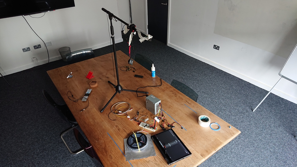 Photo of a room with a big wooden table in the centre, littered with LEDs, a prototype circuit, power supply and a laptop, with a microphone stand repurposed as a camera tripod