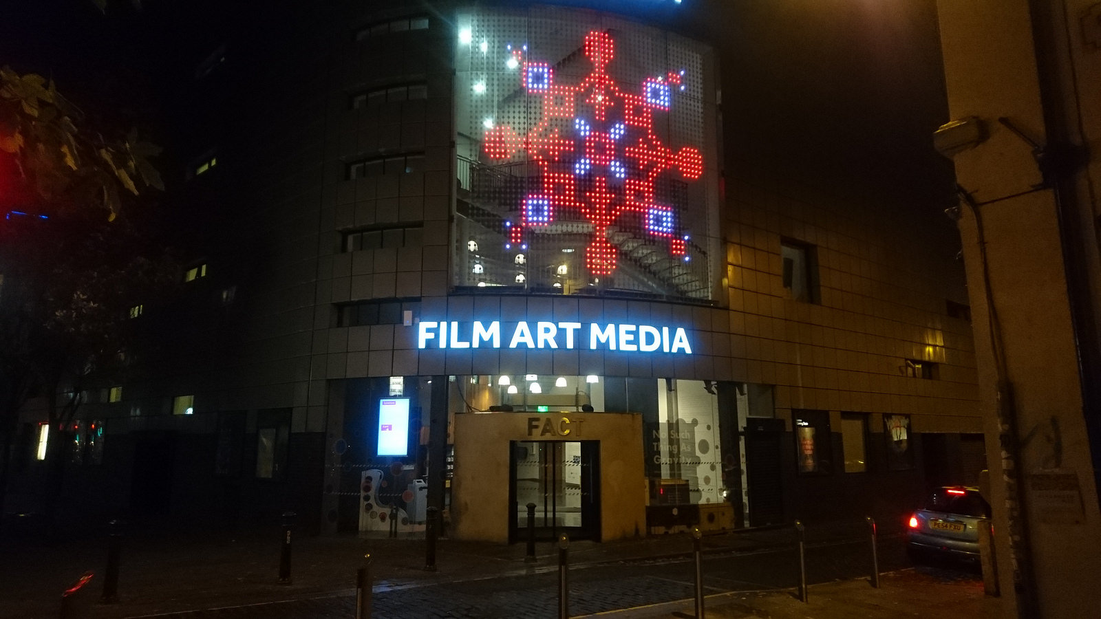A photo of the LED facade at FACT showing one of the snowflakes in red