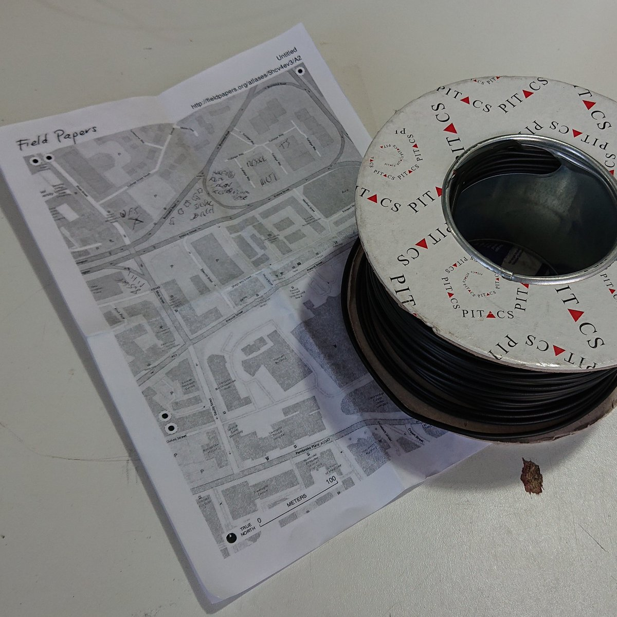 A reel of electrical wire, next to a print out of a map marked up with hand-written notes
